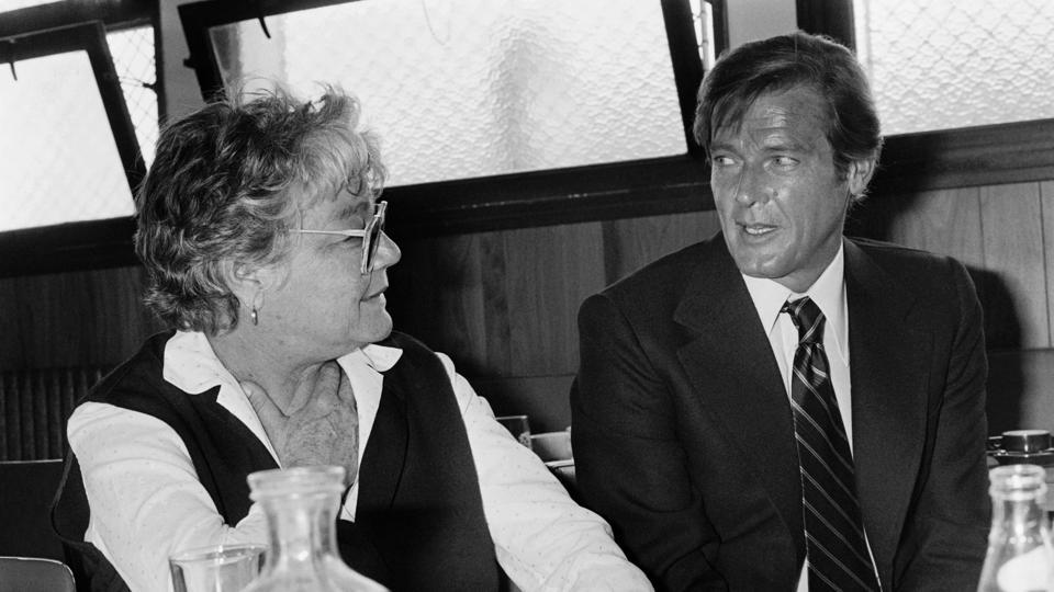 British actor Roger Moore and French actress Simone Signoret have a drink at a bar during the making of a James Bond movie at the Boulogne studios in Paris on August 29, 1978.  Along with his famous Bond role, Moore was also known for TV series The Persuaders and The Saint. (Joel ROBINE / AFP)