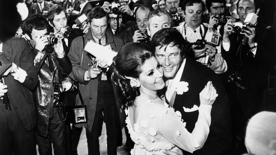 British actor Roger Moore and his new wife Italian actress Luisa Mattioli, are surrounded by the press as they dance at Caxton Hall in London following their wedding on April 12, 1969. Moore was the only actor who portrayed the popular fictional spy in seven movies between 1973 and 1985. (AFP)