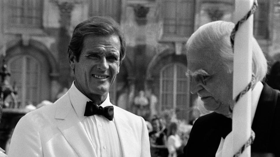 British actor Roger Moore (L) speaks with Willoughby Gray during the shooting of the James Bond film 'A View to a Kill' in Chantilly, just north of Paris on August 16, 1984, at the Chantilly Chateaux.  (Pierre VERDY / AFP)