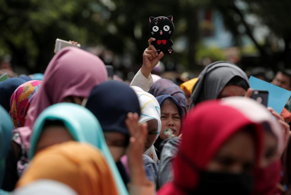 Indonesian women hold smartphones as they watch a man publicly caned for having gay sex. (REUTERS)