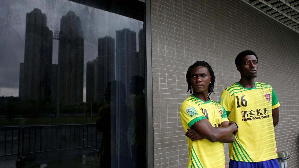 Solomon Nyassi (L), 26, from Gambia, a member of All Black FC, waits before joining a local team for a friendly match in Hong Kong, China. The team, All Black FC, is the first of its kind in the former British colony and offers a rare opportunity for refugees from more than 10 mostly African countries to integrate with residents.  (Bobby Yip/REUTERS)