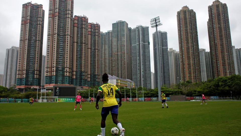 Solomon Nyassi, 26, from Gambia, a member of All Black FC, plays for a local team during a friendly match. Solomon was on a business trip to Hong Kong three years ago when his father warned him it was too dangerous to return to Gambia in west Africa.  (Bobby Yip/REUTERS)