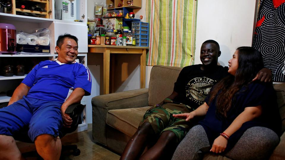 Sarjo Touray (C), 27, from Gambia shares a light moment with wife, Yukmi and his father-in-laws at their home in Hong Kong. Human rights lawyer Robert Tibbo says Hong Kong makes it difficult for them to settle permanently in the city. (Bobby Yip/REUTERS)