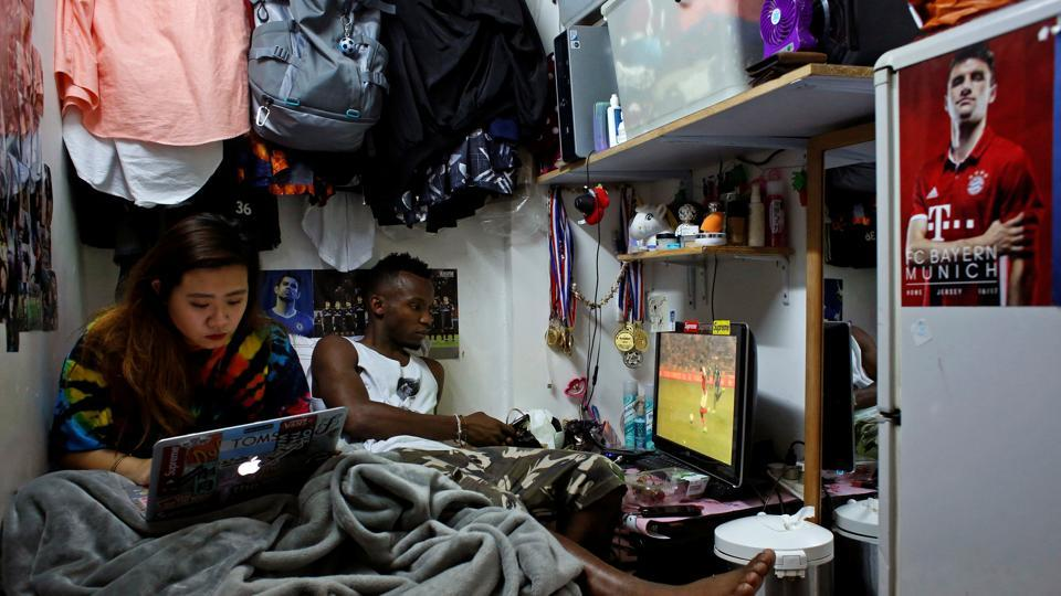 Habib Mamadou Bah, 21, and his girlfriend Karin lie on a bed at their home, a five-square-metre sub-divided unit. Eric Lee, a local player says that they don't mind their work and their personality. They just talk about football. (Bobby Yip/REUTERS)
