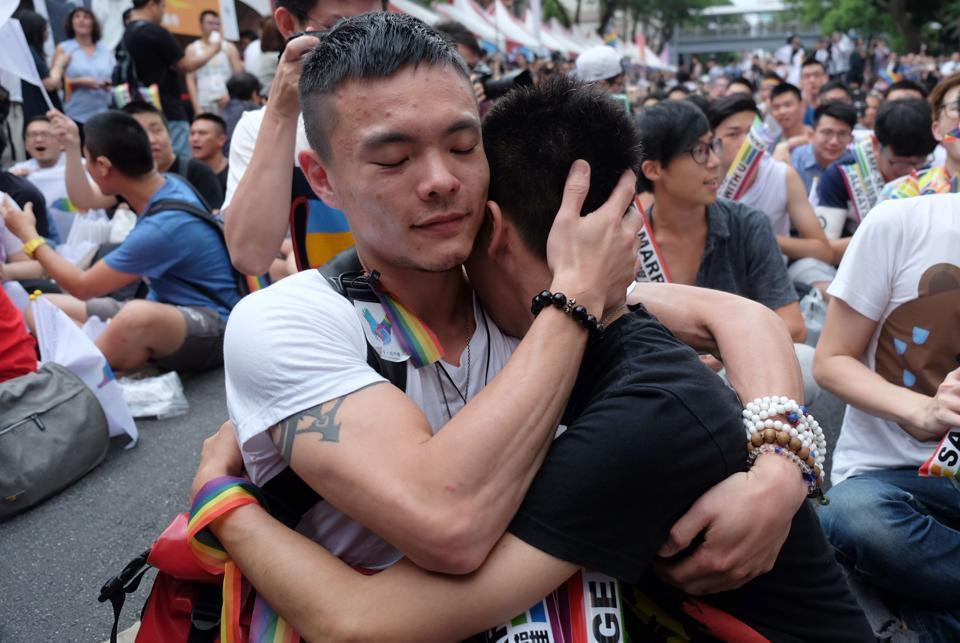 "Same-sex activists hug outside the parliament as they celebrate the landmark decision. Crowds of supporters cheered, hugged and wept as the court said current laws preventing the practice ""violated"" the Constitution's guarantees of freedom of marriage and equality. (Sam Yeh/AFP)"