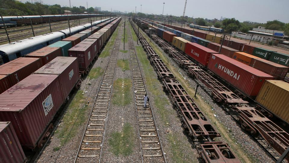 A man walks on a railway track as freight trains are parked at Tughlakabad railway station in New Delhi.