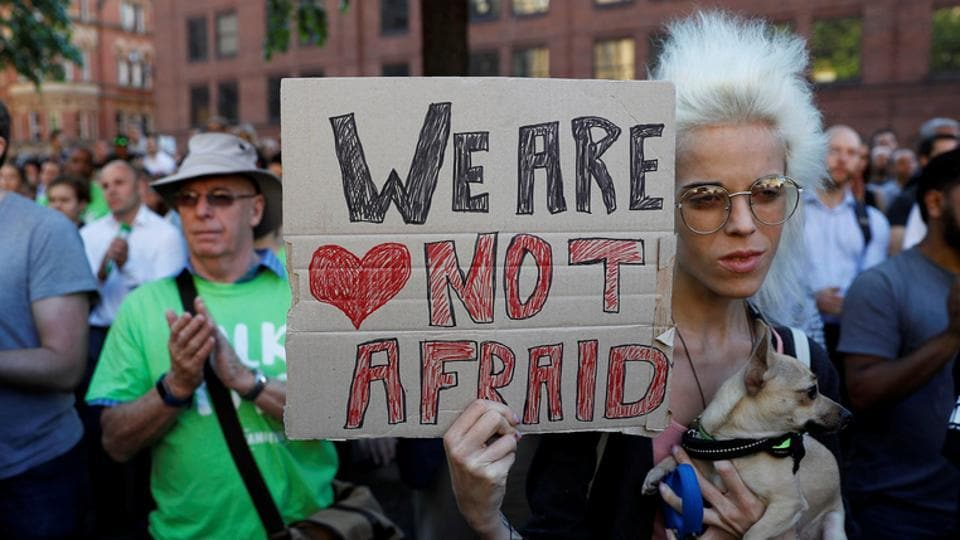 A woman holds a placard as she takes part in a vigil in central Manchester.