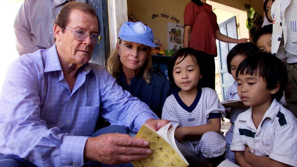 FILE PHOTO - UNICEF goodwill ambassador and former James Bond star Sir Roger Moore (L) and his wife Kristina Tholstrup read children's notebook at a kindergarden at Trieu Thuan Commune in the Vietnam's central province of Quang Tri October 28, 2003. Sir Roger was also well known for his humanitarian work - he was introduced to Unicef by the late Audrey Hepburn and was appointed as a goodwill ambassador in 1991. (Kham / REUTERS)