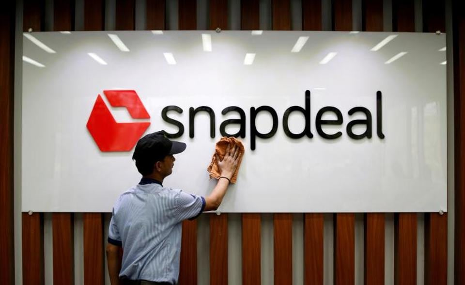 An employee cleans a Snapdeal logo at its headquarters in Gurugram .