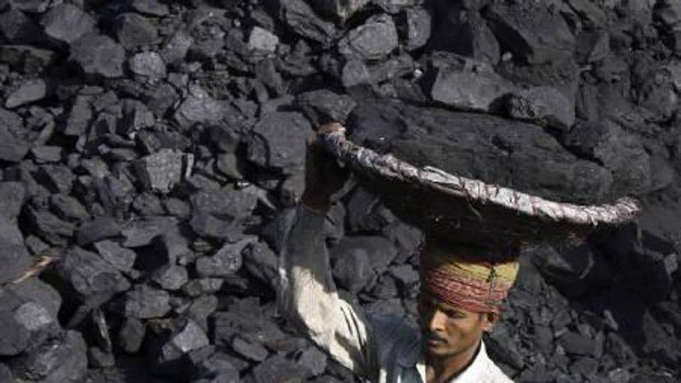 A man carrying coal at an open mine.