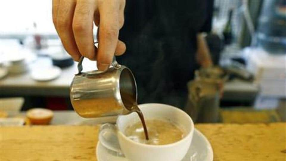 A waiter prepares cappuccino at a coffee shop.