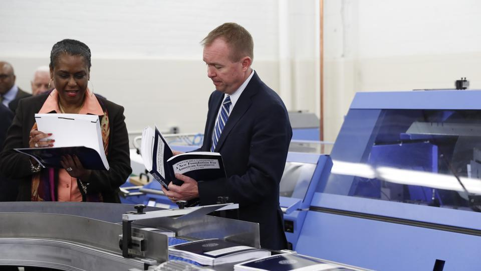 White House budget director Mick Mulvaney (right) and government publishing office director inspect the production run of US President Donald Trump's fiscal 2018 federal budget on May 19.