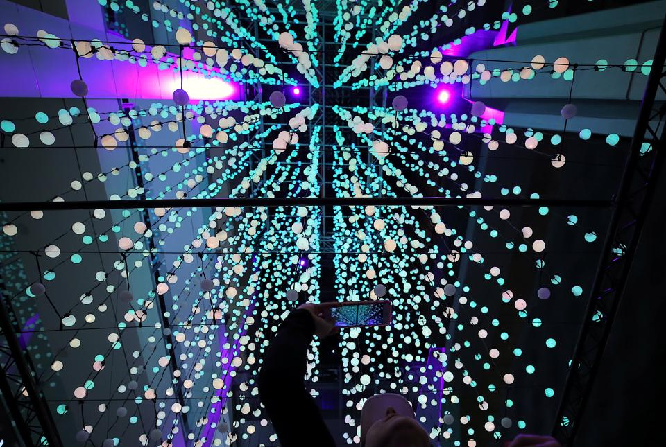 A visitor takes a photograph of an installation containing nine thousand illuminated spheres. (Steven Saphore / REUTERS)