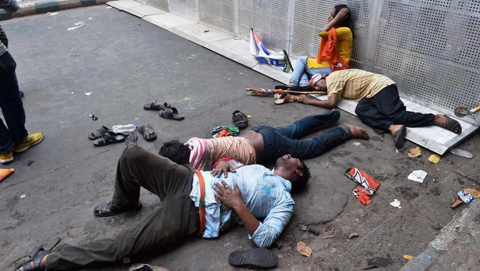 BJP activists lying on the road after being cane charged by the police. (PTI)