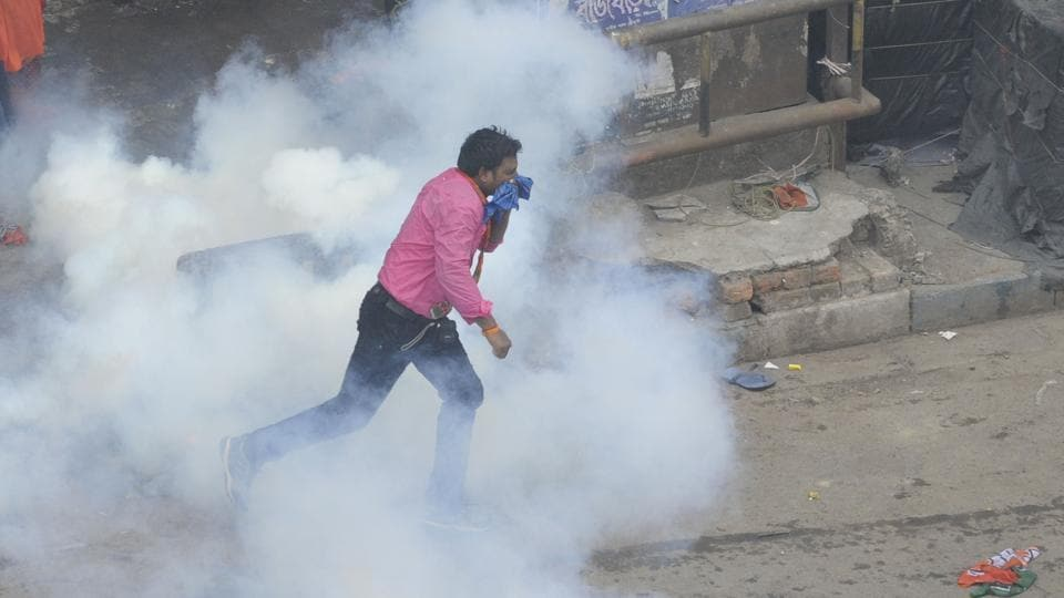 A BJP activist protects himself as he tries to evade a tear gas attack from the police. (Samir Jana/HT PHOTO)