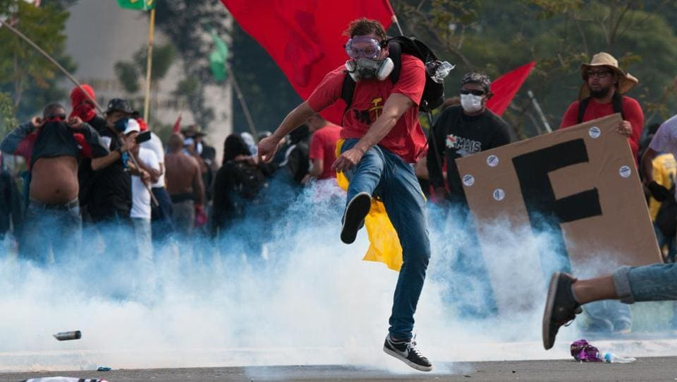 Masked protesters fired powerful fireworks at police, set ablaze furniture in the Agriculture Ministry, and sprayed anti-Temer graffiti on government buildings. (Andressa Anholete / AFP)