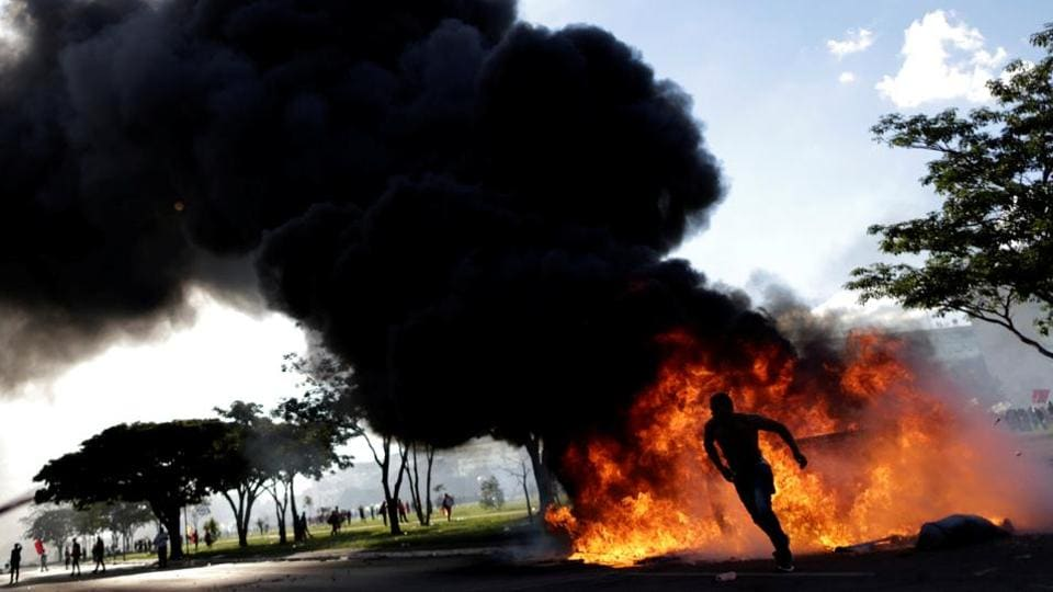 A demonstrator runs near a burning barricade during a protest against President Michel Temer, in Brasilia, Brazil. Protesters demanding the resignation of Brazilian President Michel Temer staged running battles with police and set fire to a ministry building in Brasilia on Wednesday, prompting the scandal-hit leader to order the army onto the streets. (Ueslei Marcelino / Reuters)