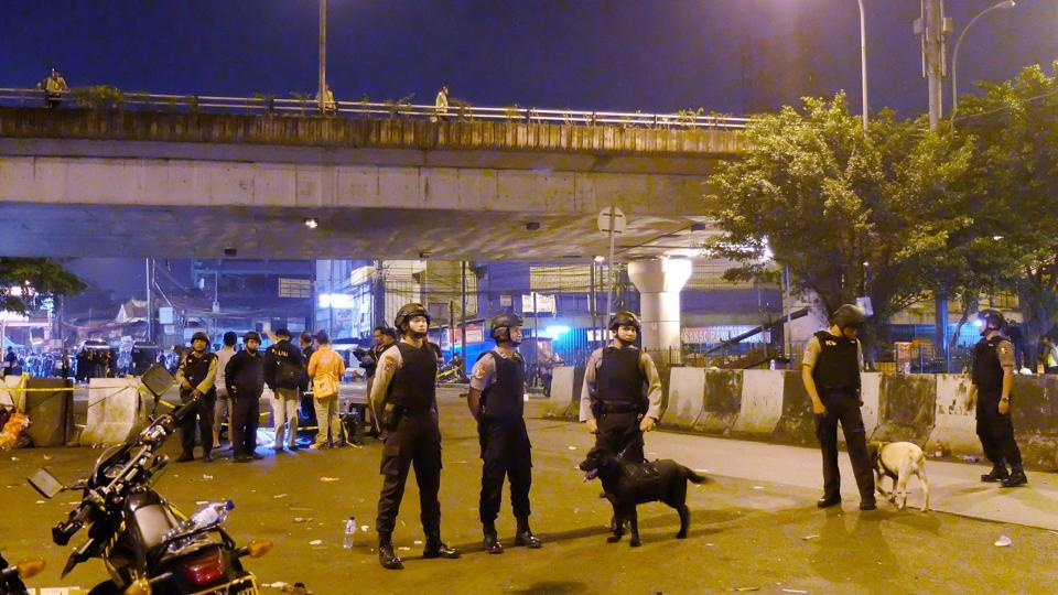 Indonesian police officers surround Kampung Melayu bus terminal in Jakarta after a bomb blast on Wednesday.