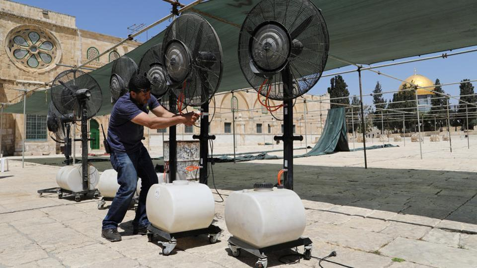 Palestinians employed by the Waqf, the Islamic trust that oversees the mosque and the ancient compound that surrounds it, set up tents for fasting worshippers to take respite from the heat alongside the golden Dome of the Rock.  (Ammar Awad/REUTERS)