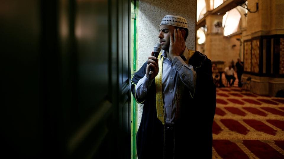 Firas Kazaz, a Palestinian muezzin dressed in traditional clothing  calls Muslims to prayer, inside al-Aqsa Mosque. The faithful believe that it was during the month of Ramadan that God revealed the first verses of the Holy Quran, Islam's sacred text to Mohammed.  (Ammar Awad/REUTERS)