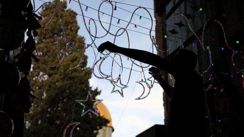 A Palestinian man hangs decorations at the entrance to the compound.  (Ammar Awad/REUTERS)