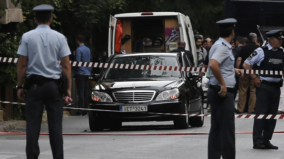 Police secure the area around the car of former Greek prime minister and former central bank chief Lucas Papademos following the detonation of an envelope injuring him and his driver, in Athens, Greece, May 25, 2017.