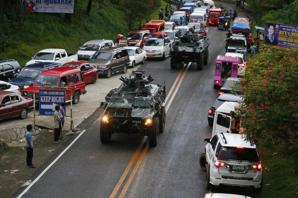 Armoured cars make their way through a queue of vehicles with fleeing residents as Muslim militants lay siege in Marawi city.