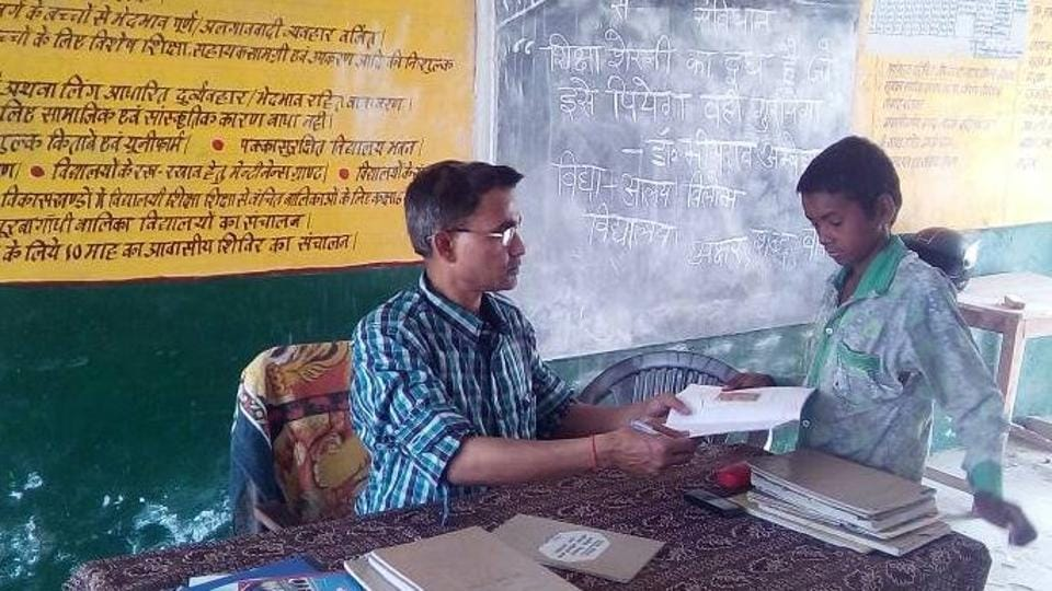 A teacher interacting with a student in the classroom at a government run primary school in Allahabad.