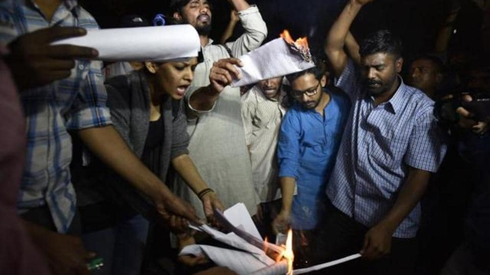 Former ABVP members who left the RSS' student outfit citing differences over its handling of the JNU row, burn a copy of the Manusmriti, in New Delhi.