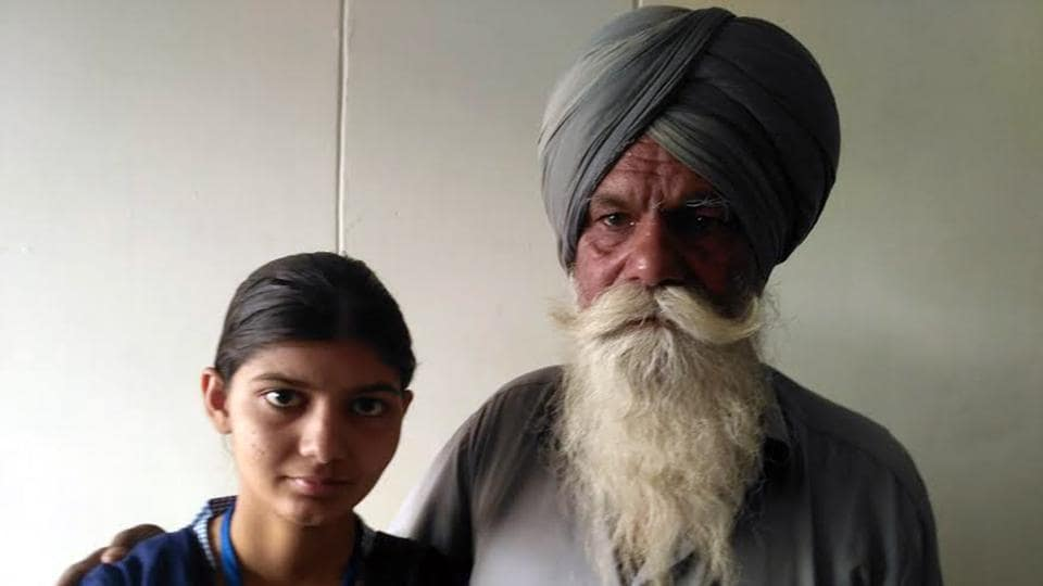 Manpreet Kaur, topper of Punjab's Sangrur district in PSEB class-10 examination with her father Bhagwan Singh, a daily wage labourer.  (HT PHOTO)