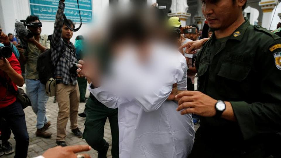 Syariah policemen hold an Indonesian man after public caning . Caning is also a punishment in Aceh for gambling, drinking alcohol, women who wear tight clothes and men who skip Friday prayers. (Beawiharta / REUTERS)