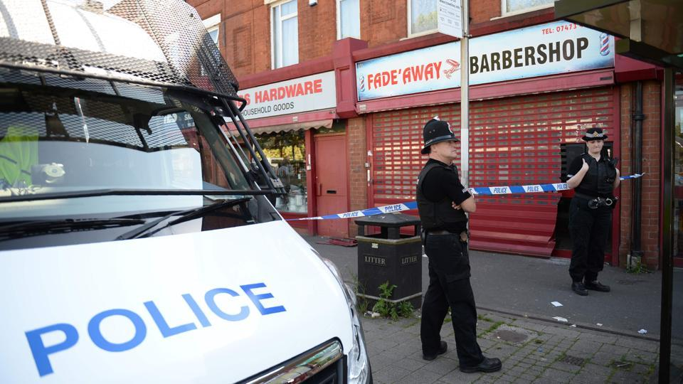 Police officers on duty outside a barber shop on Princess Road in Moss Side, Manchester, on May 26, 2017, following an early morning raid as their investigations continue into the May 22 terror attack at the Manchester Arena. Britain is hunting for a Libya-linked jihadi network thought to be behind the bombing at an Ariana Grande concert that killed 22 people.