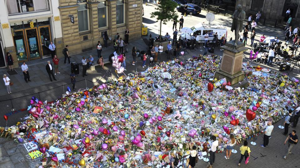People stand around flower tributes at St Ann's Square, dedicated to the victims of Monday's bombing.