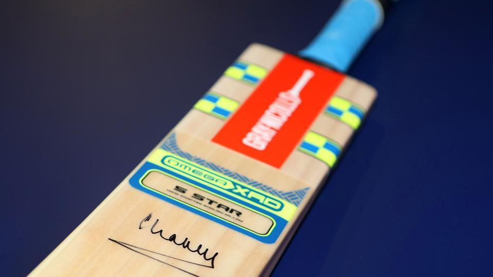 The cricket bat, signed by Britain's Prince Charles, will be donated to charity. (AFP)