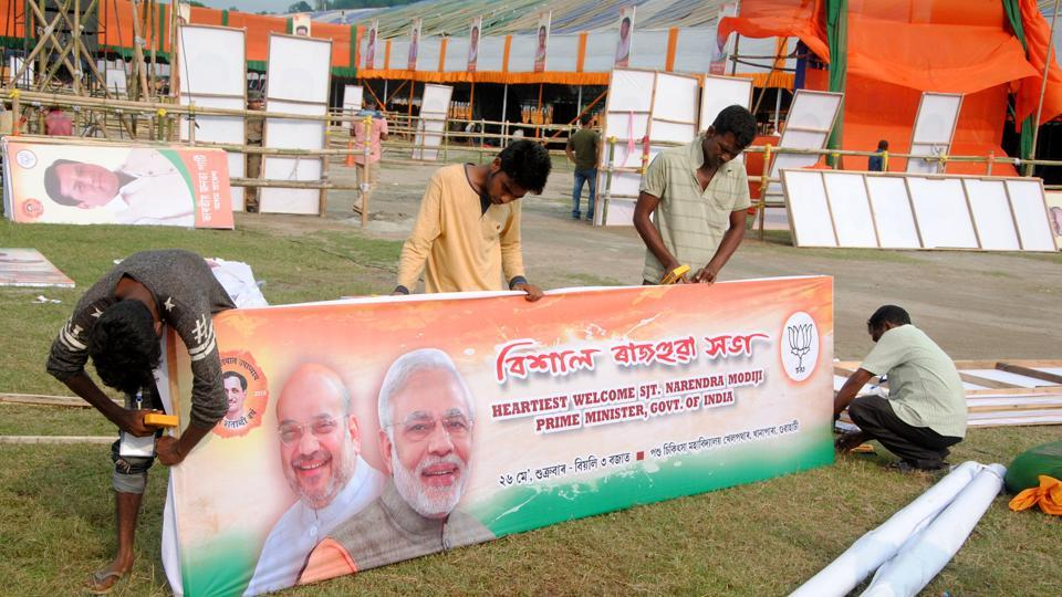 Workers busy to making posters of Prime Minister Narendra Modi at Khanapara in Guwahati on Thursday.