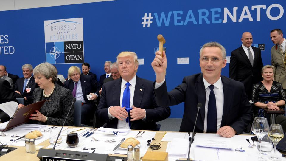 NATO Secretary General Jens Stoltenberg (R) uses a hammer during the NATO summit near U.S President Donald Trump (C) and Britain's Prime Minister Theresa May (L) at the NATO headquarters, in Brussels, Belgium, May 25, 2017.
