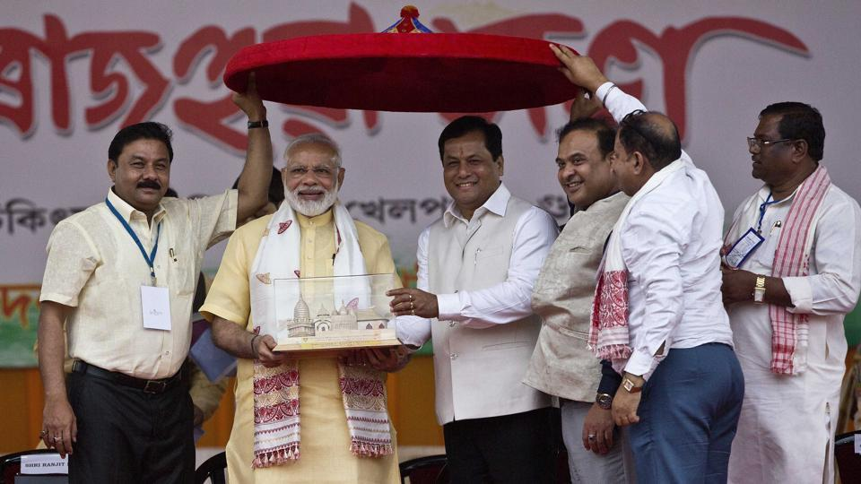 Prime Minister Narendra Modi receives a memento from Assam chief minister Sarbananda Sonowal as BJP workers hold an Assamese Japi, a traditional headgear, in Guwahati on Friday.