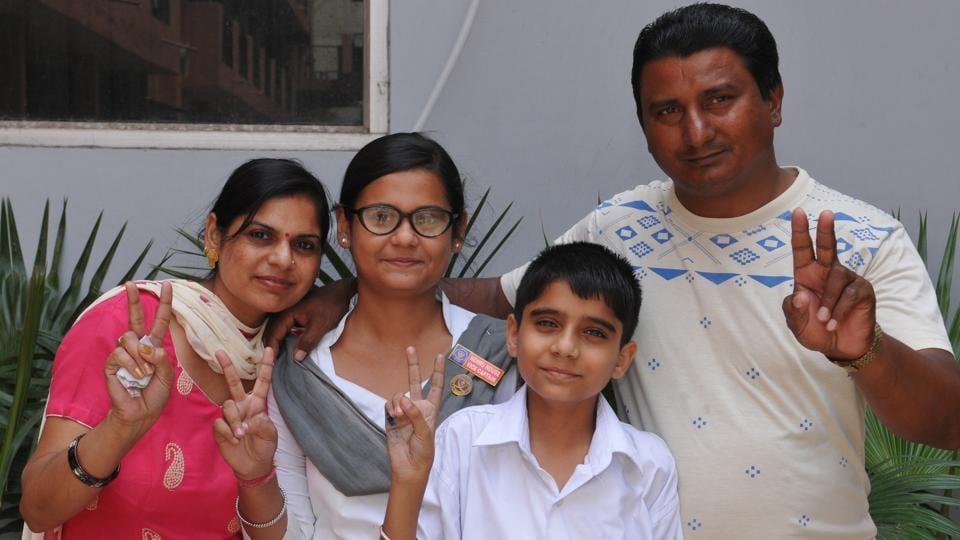 Vaishali, who ranked third in Jalandhar district with 96.46% marks, with her parents.  (HT PHOTO)