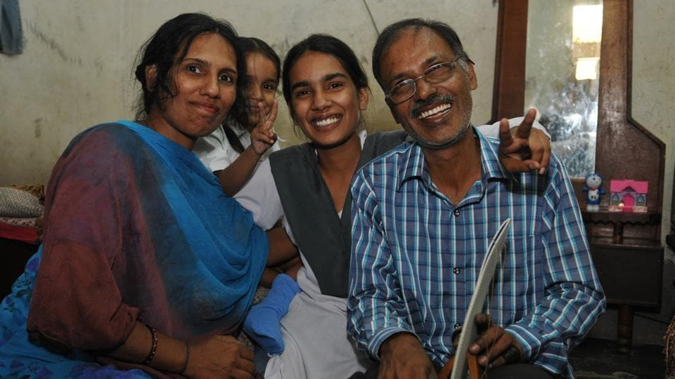 Kewal Chand who works in a football-making firm with his daughter Jyoti Mahey, Jalandhar district PSEB class-10 topper. She lives with her father, mother and a five-year-old sister in a one room house. (HT PHOTO.)