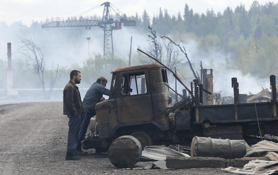 Men inspect a truck burnt during recent wildfire. (Ilya Naymushin  / Reuters)