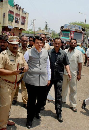 Police officials escort Maharashtra chief minister Devendra Fadnavis away from the crash site in Latur on Thursday.