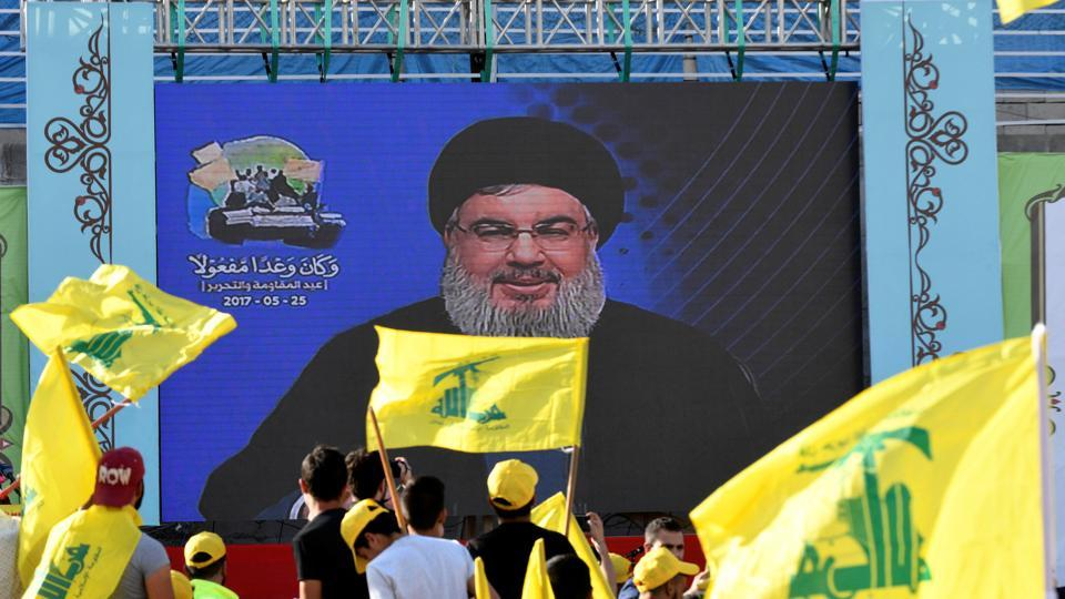 People watch Lebanon's Hezbollah leader Sayyed Hassan Nasrallah as he appears on a screen during a live broadcast to speak to his supporters at an event marking Resistance and Liberation Day in Bekaa Valley, Lebanon, May 25, 2017.