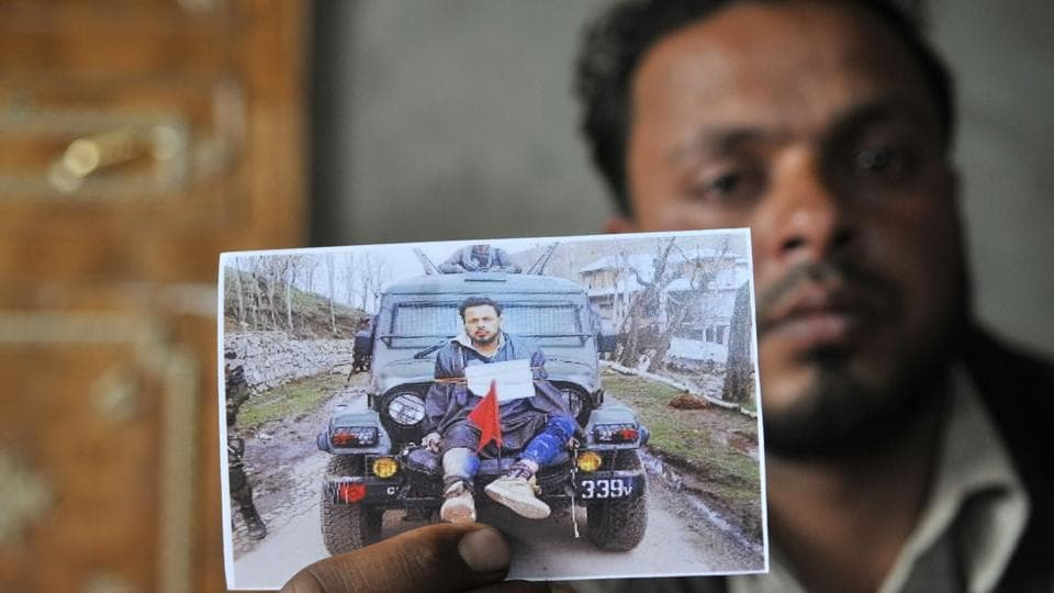Farooq Dar, who was used as a human shield by army, sits in his home in Chil village in Budgam district and holds a picture of him being tied on a jeep.