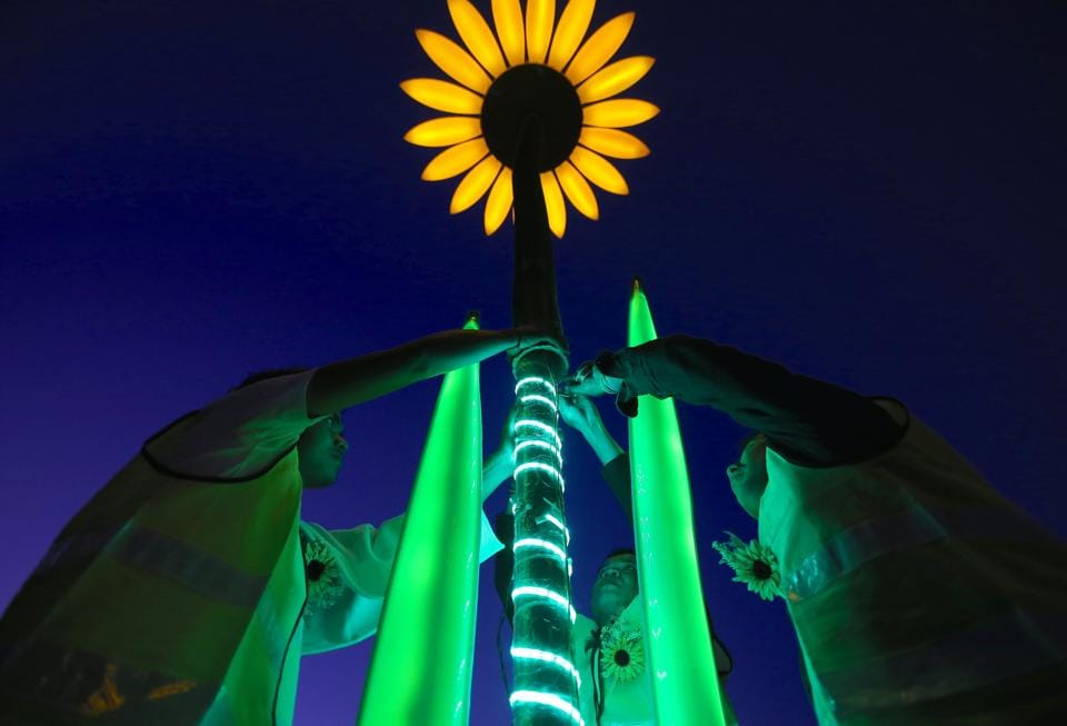 Workers make finishing touches to an illuminated sunflower installation during a preview at The Royal Botanic Garden. (REUTERS)