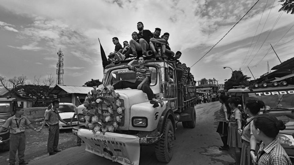 Volunteers travel on a truck with the coffins from the morgue to the Lamka Public Ground as the public pays their last respect to the dead.  The initial demands by the tribes included quashing of the bills, justice for the dead and a separate administration for the hill areas.  (Ravi Choudhary/HT PHOTO)