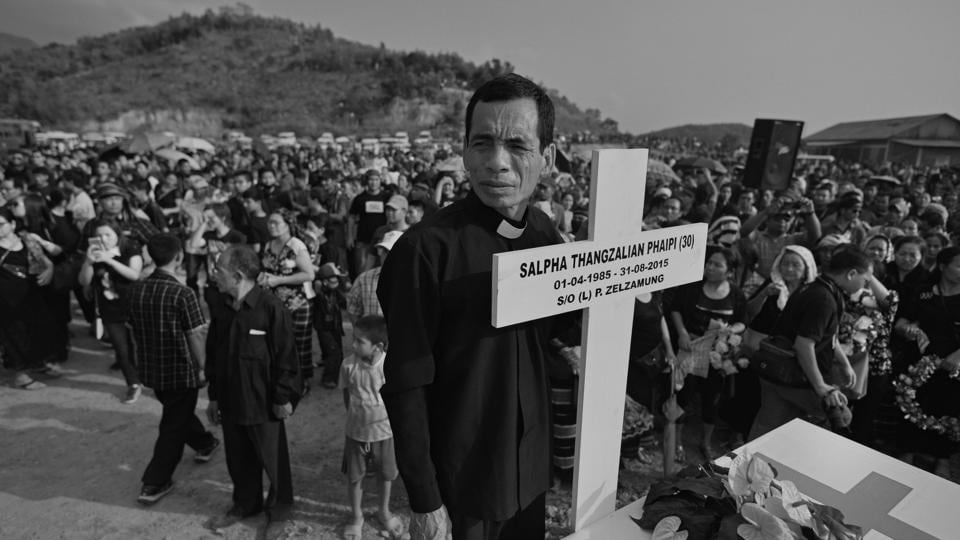 A pastor holds a wooden cross at the graveyard. On May 10 this year, an agreement was reached between the tribal leaders and the Manipur government in the form of a memorandum of understanding (MoU) – on condition that the dead should be buried by May 25.  (Ravi Choudhary/HT PHOTO)