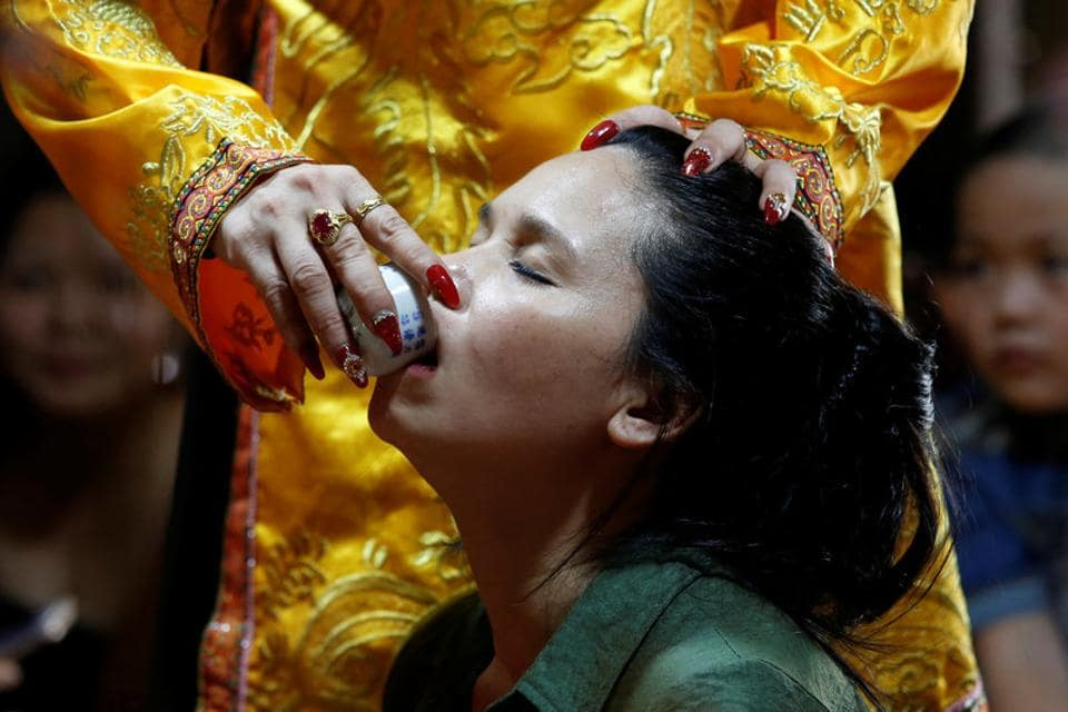 Pham Thi Thanh drinks a glass of water used as a treatment during a medium ritual at a Hau Dong ceremony. Thanh said the appeal of the ritual had broadened as it could attract participants of either gender. (Kham/REUTERS)