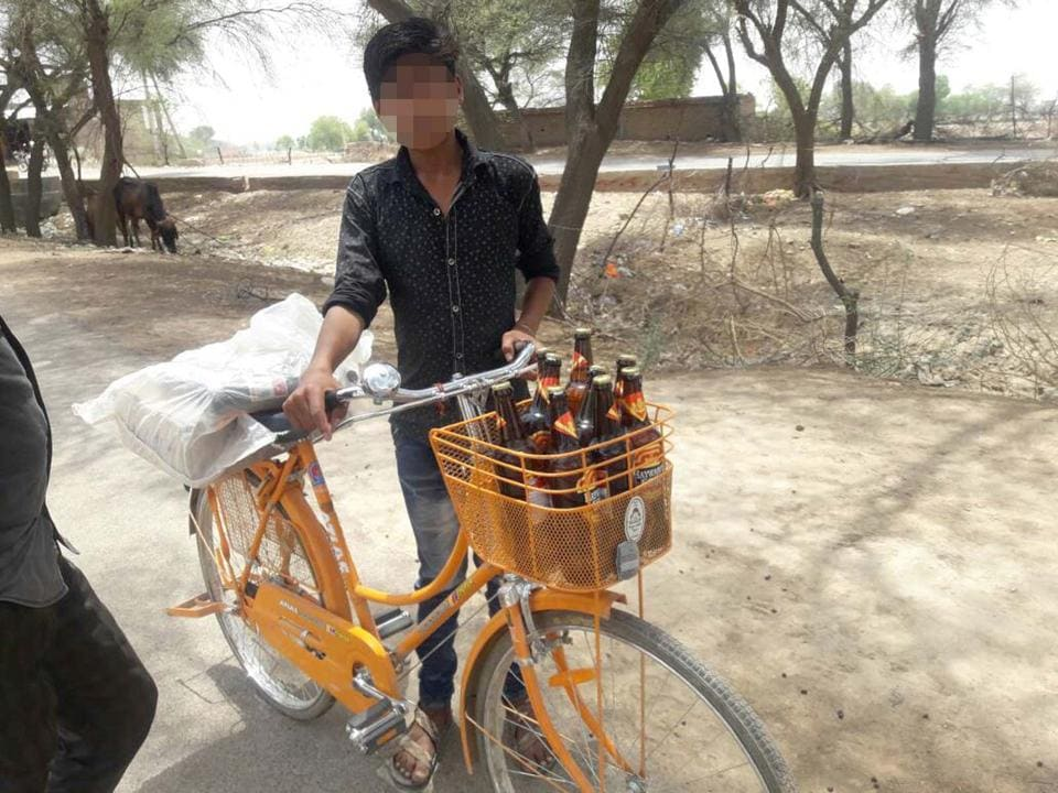 A minor carries bottles of beer on a bicycle that government hands out to schoolgirls, in Bikaner. (The boy's face has been blurred to protect his identity since he is a minor)