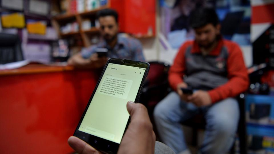 Three men browse the internet on mobile phones at a shop in Srinagar. Authorities have once again suspended mobile internet services.