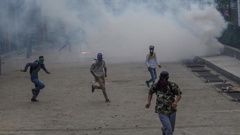 Masked Kashmiri protesters chase Indian policemen during a protest in Srinagar on May 26.